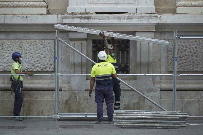 Varios operarios montan un andamio en un edificio del centro de Sevilla.