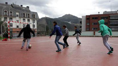 Varios niños juegan al futbol ajenos al humo del vertedero que tienen al fondo.