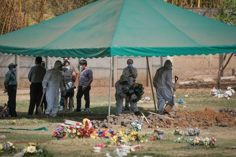 Sepultureros durante un entierro de un paciente sospecho de covid-19, en la ciudad de Ticuantepe, en Nicaragua.