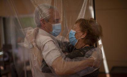 Una mujer recibe un abrazo a través de una pantalla de plástico en una residencia de Barcelona.