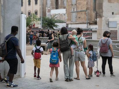 Varios padres acompañan a sus hijos a la entrada de la escuela Xirinacs en el barrio del Eixample Esquerra de Barcelona.