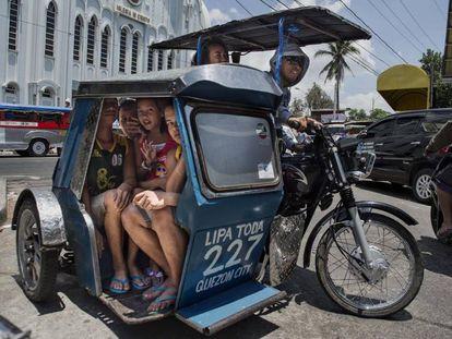 Varias mujeres viajan en un triciclo, los mototaxis de Filipinas.