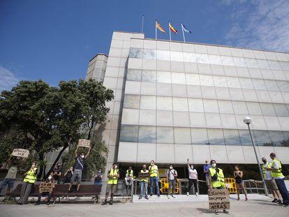 Una docena de trabajadores afectados por ERTE protestan frente a la delegación en Barcelona del SEPE.