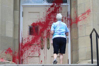 Una feligresa se acerca a la entrada de la iglesia presbiteriana Grace atacada con pintura roja en Calgary, el pasado día 3.