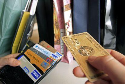 Una persona saca una tarjeta de la cartera para pagar.