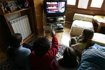 Un grupo de niños observa las emisiones de televisión.