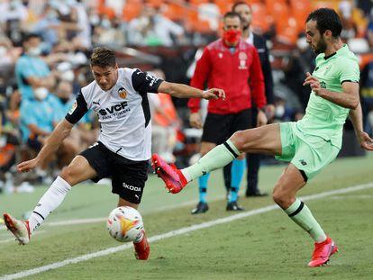 El delantero del Valencia Manu Vallejo disputa el balón ante el defensa del Athletic Íñigo Lekue en Mestalla.