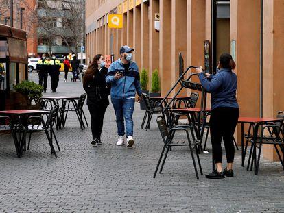 Una camarera prepara la terraza del restaurante donde trabaja para atender a sus clientes al mediodía.