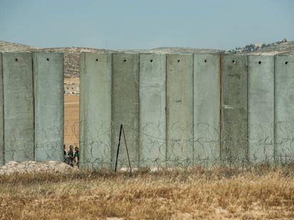"""<a href=""""http://elpais.com/elpais/2017/05/31/album/1496247003_088581.html""""><b>FOTOGALERÍA:</B></A> Palestinos cruzando la parte aún abierta del muro de Cisjordania, en Yata."""