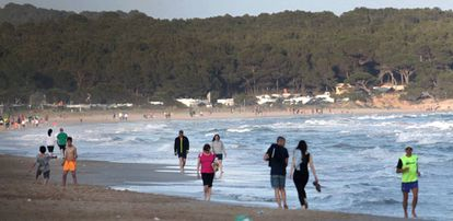Gente paseando por la orilla de la Playa Llarga (Playa Larga) en Tarragona.