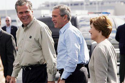 El gobernador de Florida, Jeb Bush (izquierda); su hermano, el presidente Bush, y su esposa, Laura, ayer en Florida.