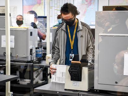 Trabajadores procesan papeletas de voto anticipado en Miami.
