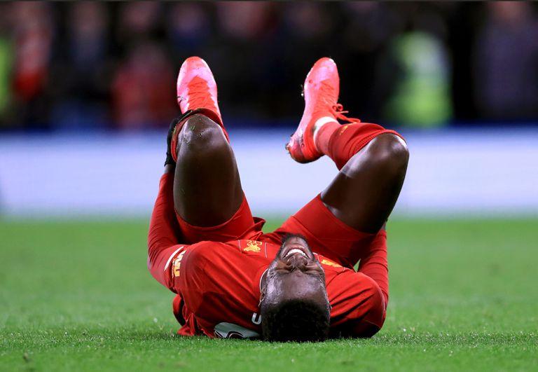 Origi, tendido sobre el césped, se duele durante el partido contra el Chelsea en Stamford Bridge.