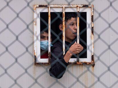 Dos jóvenes miran por una ventana de un centro temporal de Ceuta, este jueves.