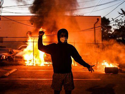 Un manifestante levanta el puño ante unos coches quemados, el pasado viernes, en Minneapolis.