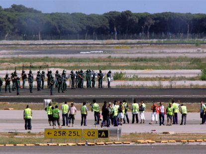 En primer término, los trabajadores de Iberia ocupan, el viernes pasado, las pistas de El Prat. Al fondo, agentes antidisturbios de la Guardia Civil.