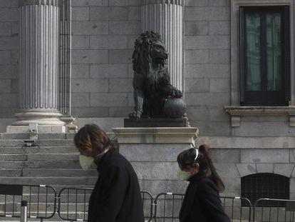 Dos transeúntes caminan frente al Congreso de los Diputados protegidos con mascarillas.