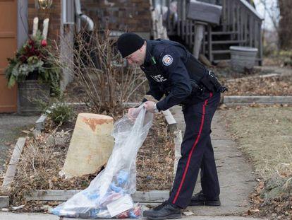 Un policía investiga en el jardín de una de las viviendas de Toronto donde trabajaba el acusado.