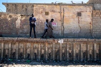 El teniente de alcalde de Saint Louis, Latyr Fall, posa junto al antiguo muro de hormigón, construido en 1930 por el régimen colonial francés para proteger a la ciudad del mar.