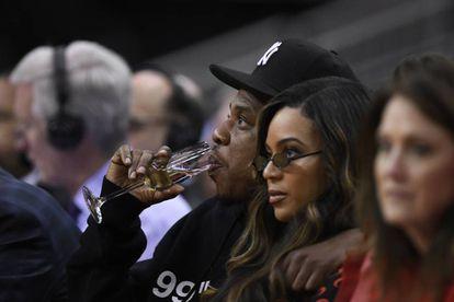 Jay-Z bebe champán sentado al lado de su esposa, la cantante Beyoncé, durante un partido de la NBA el pasado mayo.