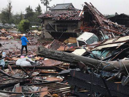Un hombre camina por los escombros de varias casas desplomadas por el tifón Hagibis en Ichihara, al este de Tokio.