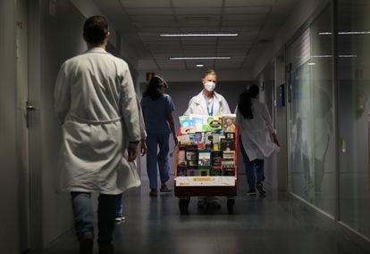 Marisa Guerra, una de las responsables de la biblioteca para pacientes del hospital Clínico, empuja el carrito cargado de libros.