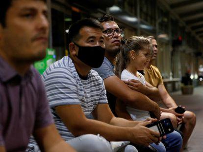 El hermano mayor un intérprete afgano espera a que su hermano menor llegue desde Fort Lee, Virginia, al aeropuerto de Sacramento, California, el 5 de agosto.