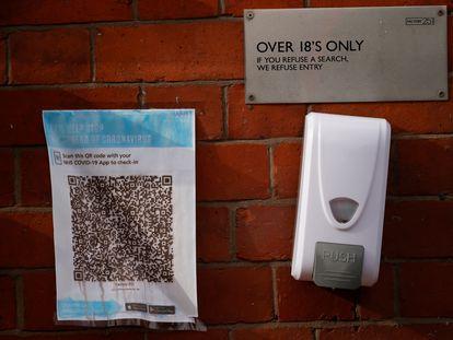 Un código QR para la app del sistema de salud británico en la entrada de un bar en Manchester (Reino Unido) junto a un dispensador de gel.