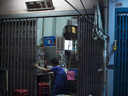 Una mujer entra en su casa de Bangkok. En la televisión se emite una telenovela.