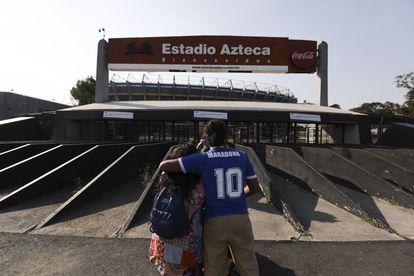 Una pareja de aficionados rinde homenaje a Maradona a las puertas del estadio Azteca de México.