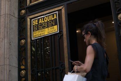 Una mujer pasa ante un portal en Madrid con un anuncio de un piso en alquiler, en julio.