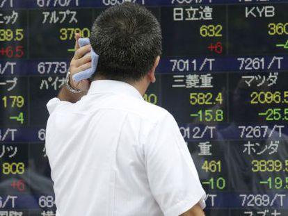 Un inversor observa un panel de cotizaciones en Tokio (Japón).