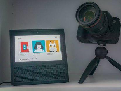 Amazon Echo Show en una estantería junto a una cámara de fotos