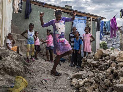 Una niña del barrio de Jalousie baila entre las chabolas ante la mirada divertida de sus amigos.