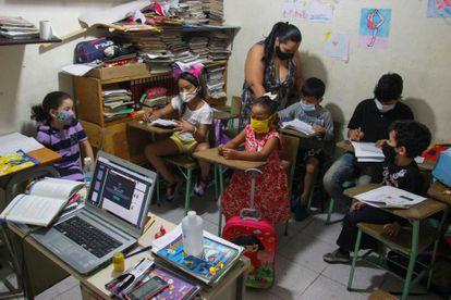 La maestra Socorro Medina y sus alumnos, en la escuela que ha montado en su vivienda, en el barrio de La Cruz de Caracas, Venezuela.