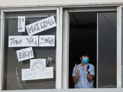 Una enfermera sale a la ventana de una de las habitaciones del Hospital Virgen del Camino de Pamplona para participar también en el aplauso hacia sus compañeros
