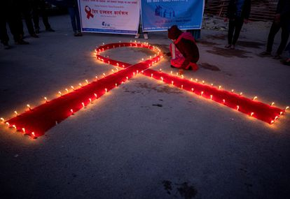 Mujeres y niños del orfanato de rehabilitación para enfermos de sida 'Maiti Nepal', encienden varias velas de manera que forman un lazo rojo en Katmandú (Nepal).