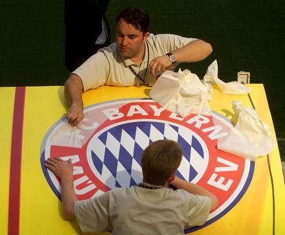 Unos trabajadores colocan un escudo del Bayern de Múnich, en el estadio de San Siro, un día antes de la final de la Copa de Europa contra el Valencia FC en 2001