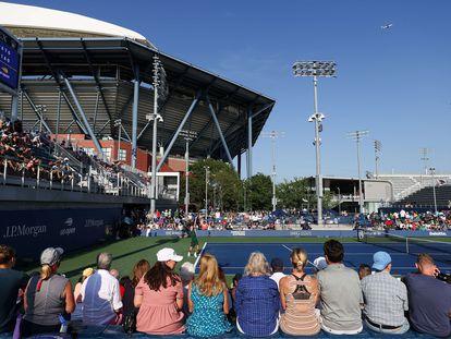 Aficionados presencian un partido en la primera jornada del US Open, con la Pista Arthur Ashe al fondo.