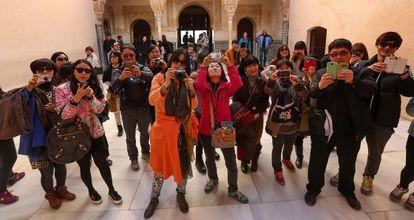 Un grupo de turistas fotografía la Alhambra.