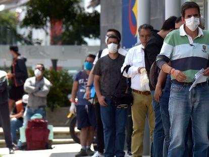 Un grupo de hombres hace fila para entrar a un banco en su día de 'Pico y Género'.