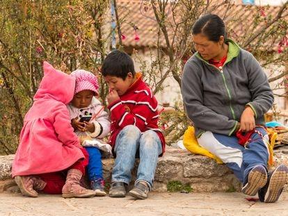 Una mujer indígena vigila a sus hijos que juegan con un teléfono móvil en Chinchero, Perú, en 2015.