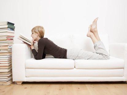 Una mujer lee un libro en un sofá.