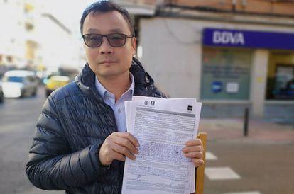 Enguan Chen muestra su hoja de reclamación ante la sucursal del BBVA en Usera.