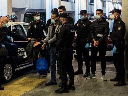 Dos jóvenes migrantes marroquíes, esposados llegan al aeropuerto de Las Palmas (Canarias), para ser deportados por la policía en diciembre de 2020.