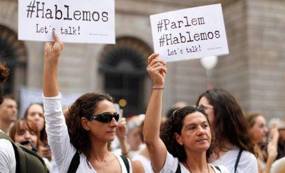 Dos mujeres sostienen carteles a favor del diálogo este sábado en Barcelona.