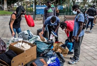 Jóvenes senegaleses recogen ropa donada por los ciudadanos en una iniciativa de la plataforma ciudadana Somos Red, en febrero en Gran Canaria.