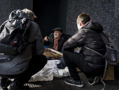 Una persona sin hogar atiende a dos educadores de Arrels, en una imagen de archivo.