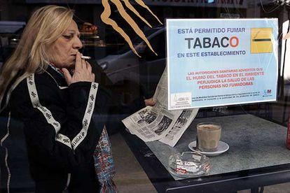 Una mujer fuma en un establecimiento en el que está permitido consumir cigarrillos.