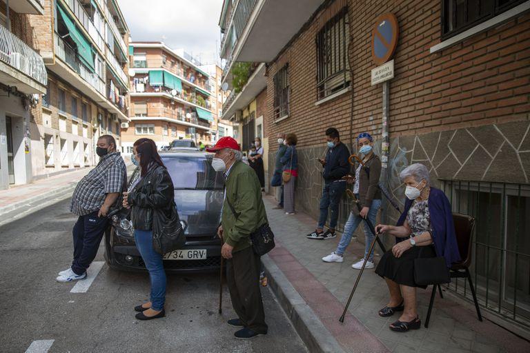Un grupo de vecinos esperan su turno frente a la entrada del centro de salud Puerta Bonita, en Madrid.